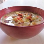 corn chowder with bacon in red bowl