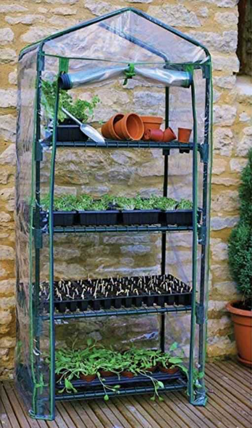 4 shelves structure with trays of seedlings growing and a plastic zip up enclosure