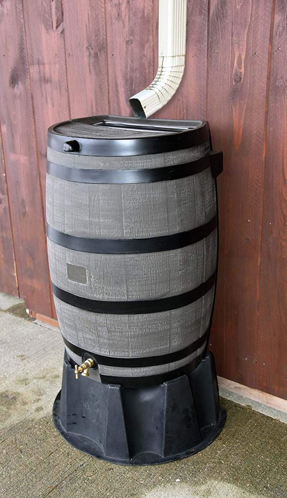 RTS Home Accents 50-Gallon Flat Back Rain Barrel next to wood fence.