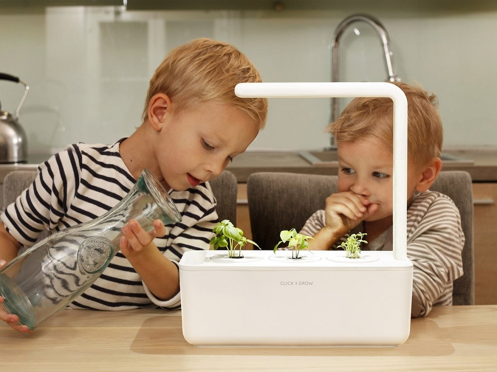 Two young children filling the click and grow 3 with water