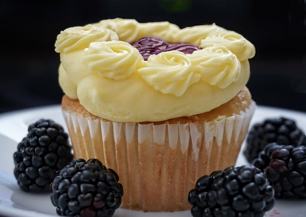 Cupcake with lemon flavored icing served with blackberries