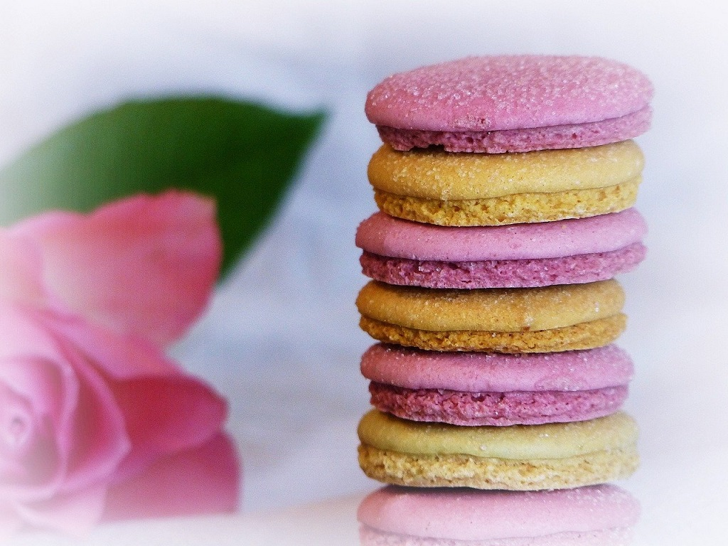 stack of pink and yellow macaroons with rose garnish