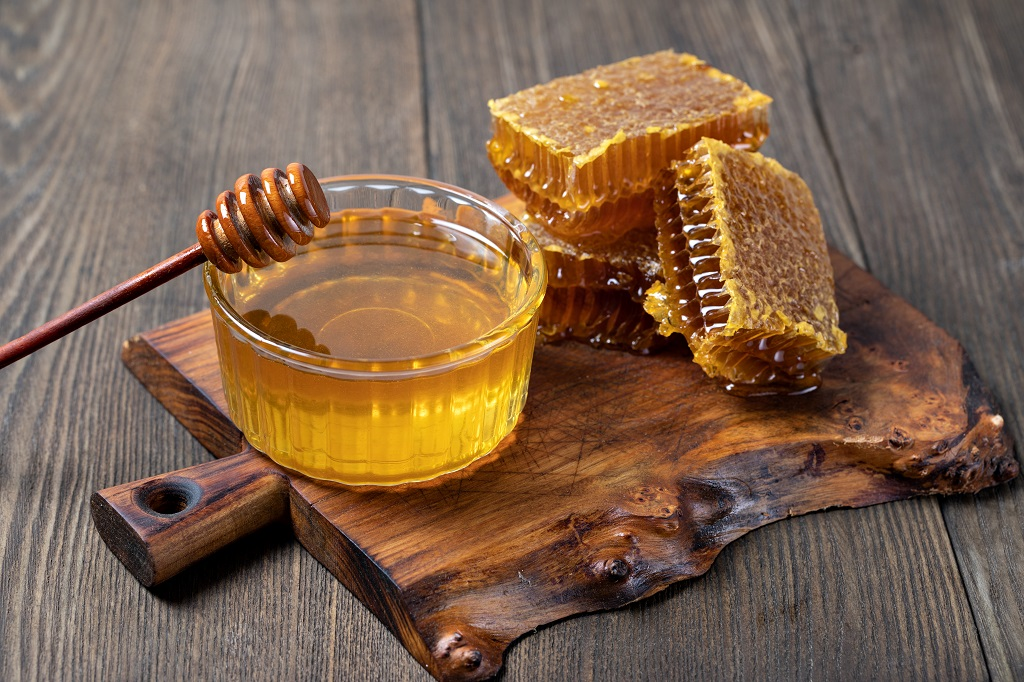 raw honey comb with honey jar