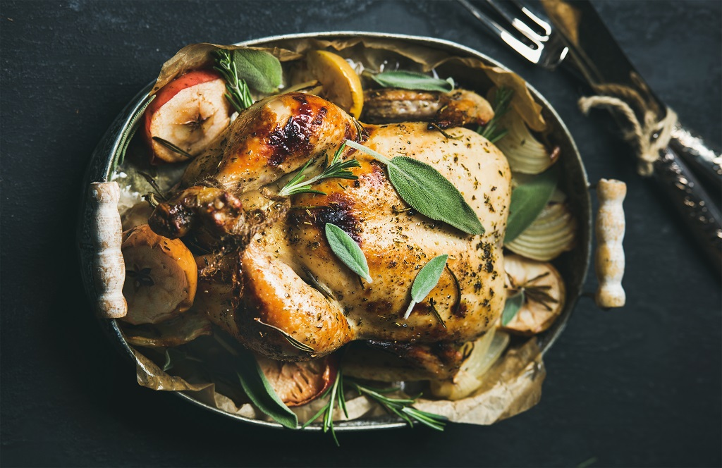 browned whole chicken breast with apples and sage in a cooking pot