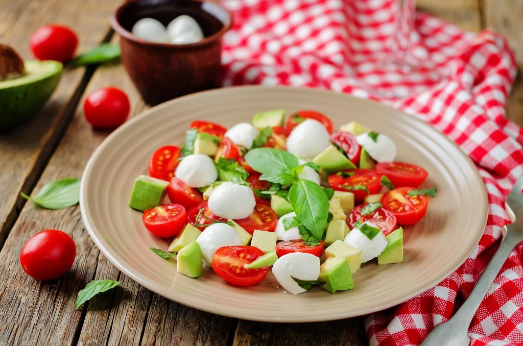 Salad with avacado, basil, tomatoes and cheese