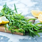 tarragon and lemon wedges on a cutting board