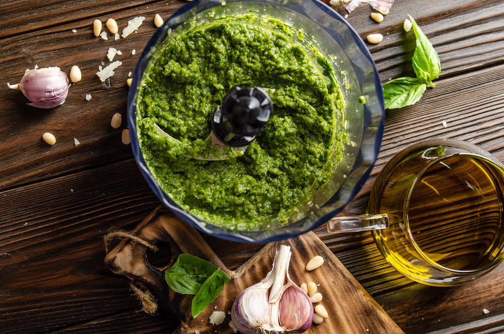 pesto in food processor with garlic cloves basil and olive oil on the cutting board