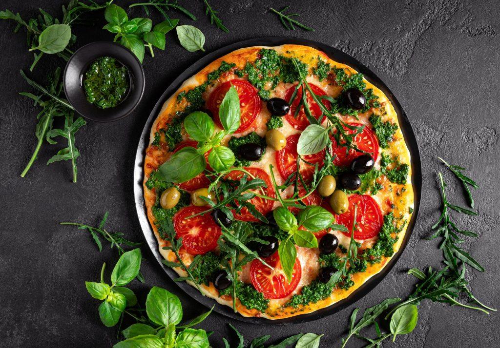 homemade pizza with basil and pesto sauce