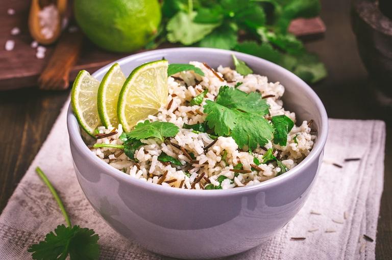 bowl of basmati rice lime and fresh cilantro leaves