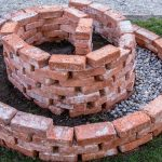 red bricks laid in a circular design to build the base of the spiral herb garden
