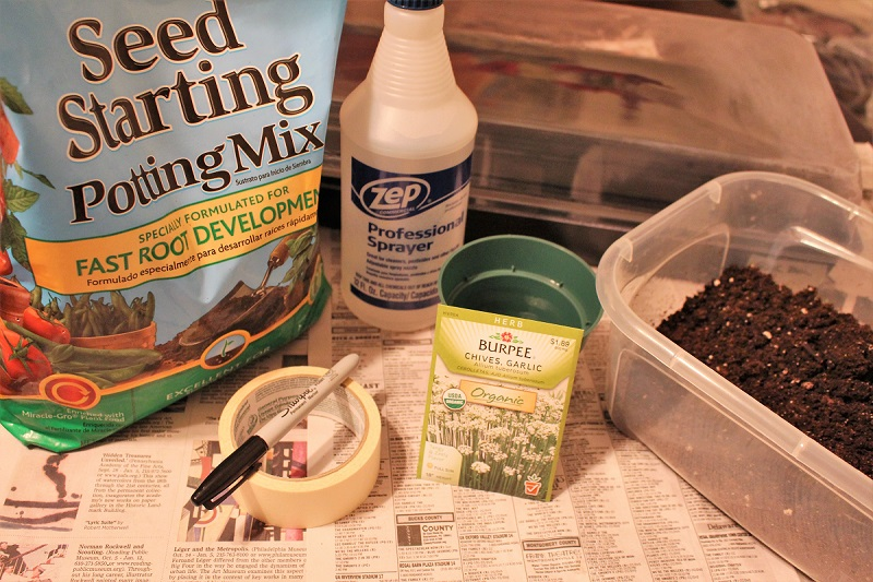 Seed starting mix and other seed starting supplies on a table covered with newpaper