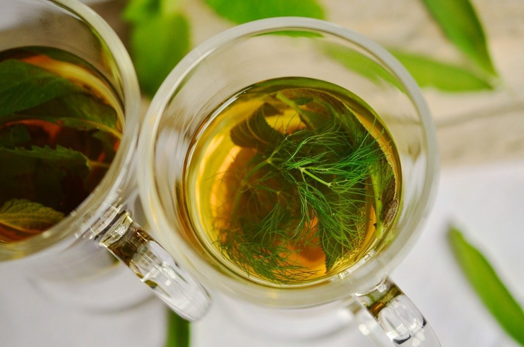 herbal tea with fennel leaves floating in the cup
