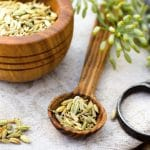 fennel seeds in a spoon on a table - background of fennel blooms, scissors and a bowl of seeds