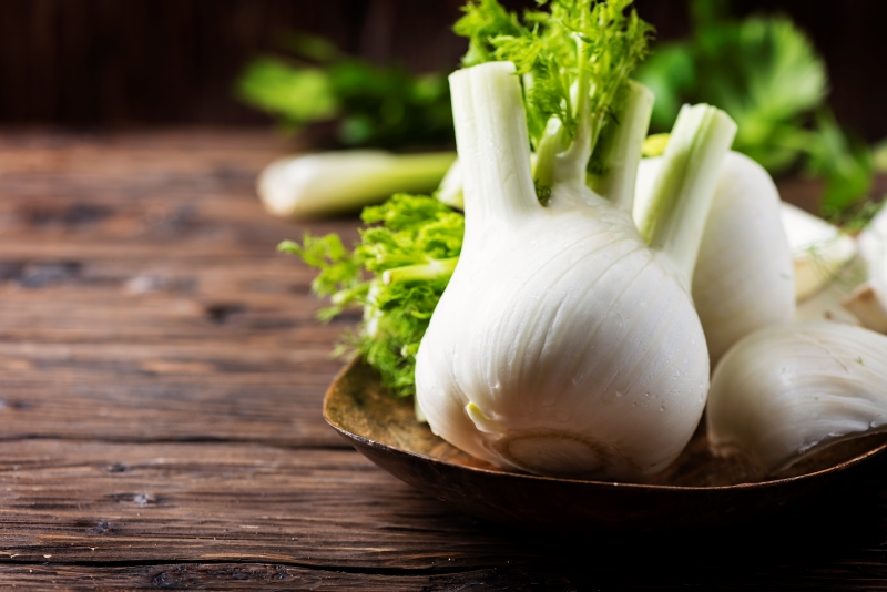 big white fennel bulbs in a wooden dish